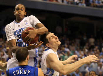 GREENSBORO, NC - MARCH 13:  John Henson #31 of the North Carolina Tar Heels rebounds a shot by teammate Tyler Zeller #44 as Seth Curry #30 of the Duke Blue Devils looks on during the second half in the championship game of the 2011 ACC men's basketball to