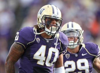 SEATTLE - SEPTEMBER 11:  Linebacker Mason Foster #40 of the Washington Huskies celebrates with Willis Wilson #29 after tackling quarterback Ryan Nassib #12 of the Syracuse Orange and causing a fumble on September 11, 2010 at Husky Stadium in Seattle, Wash