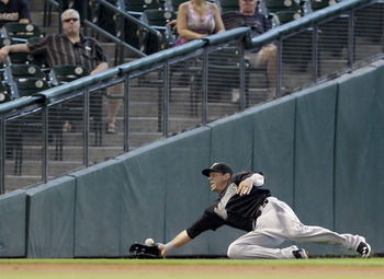HOUSTON,TX- APRIL 10 : Left fielder Logan Morrison #20 of the Florida Marlins can't quite catch Michael Bourn of the Houston Astros double in the first inning in a MLB  baseball game on April 10, 2011 at Minute Maid Park in Houston, Texas. (Photo by Thoma