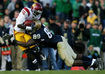 SOUTH BEND, IN - OCTOBER 17: Defensive end Kapron Lewis-Moore #89 of the Notre Dame Fighting Irish tackles  wide receiver Damian Williams #18 of the USC Trojans in the second quarter of the game at Notre Dame Stadium on October 17, 2009 in South Bend, Ind