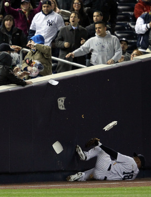 NEW YORK, NY - APRIL 05:  Andruw Jones #18 of the New York Yankees is hit with a fans onion rings as a foul ball hit by Jason Kubel #16 of the Minnesota Twins lands in the stands at Yankee Stadium on April 5, 2011 in the Bronx borough of New York City.  (