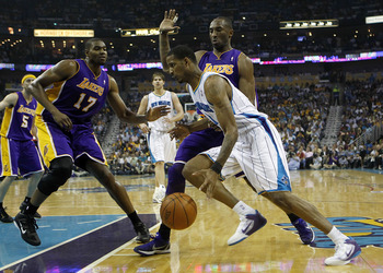 NEW ORLEANS - APRIL 24:  Trevor Ariza #1 of the New Orleans Hornets drives by Kobe Bryant #24 and Andrew Bynum #17 of the Los Angeles Lakers in Game Four of the Western Conference Quarterfinals in the 2011 NBA Playoffs at New Orleans Arena on April 24, 20