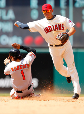 CLEVELAND - APRIL 17:  Orlando Cabrera #20 of the Cleveland Indians turns the double play on Brian Roberts #1 of the Baltimore Orioles during the game on April 17, 2011 at Progressive Field in Cleveland, Ohio.  (Photo by Jared Wickerham/Getty Images)