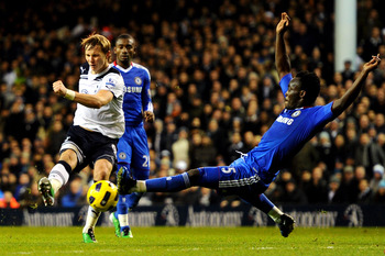 LONDON, ENGLAND - DECEMBER 12: Roman Pavlyuchenko of Spurs has his shot on goal blocked by Michael Essien of Chelsea during the Barclays Premier League match between Tottenham Hotspur and Chelsea at White Hart Lane on December 12, 2010 in London, England.