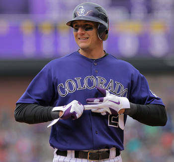 DENVER, CO - APRIL 20:  Shortstop Troy Tulowitzki #2 of the Colorado Rockies removes his batting gloves after taking an at bat against the San Francisco Giants at Coors Field on April 20, 2011 in Denver, Colorado.  (Photo by Doug Pensinger/Getty Images)