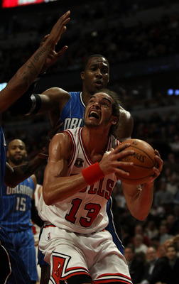 CHICAGO, IL - DECEMBER 01: Joakim Noah #13 of the Chicago Bulls goes up for a shot against Dwight Howard #12 of the Orlando Magic at the United Center on December 1, 2010 in Chicago, Illinois. The Magic defeated the Bulls 107-78. NOTE TO USER: User expres