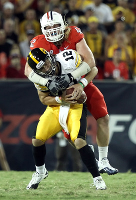 TUCSON, AZ - SEPTEMBER 18:  Quarterback Ricky Stanzi #12 of the Iowa Hawkeyes is sacked by Brooks Reed #42 of the Arizona Wildcats during the third quarter of the college football game at Arizona Stadium on September 18, 2010 in Tucson, Arizona.  The Wild