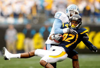 CHARLOTTE, NC - DECEMBER 27:  Deunta Williams #27 of the North Carolina Tar Heels tackles Alric Arnett #82 of the West Virginia Mountaineers during the Meineke Car Care Bowl on December 27, 2008 at Bank of America Stadium in Charlotte, North Carolina.  (P