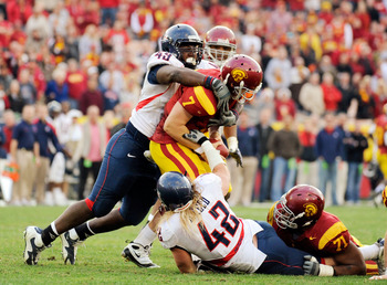 LOS ANGELES, CA - DECEMBER 05:  Quarterback Matt Barkley #7 of the USC Trojans is sacked by Earl Mitchell #49 and Brooks Reed #42 of the Arizona Wildcats during the fourth quarter of the NCAA college football game at the Los Angeles Coliseum on December 5