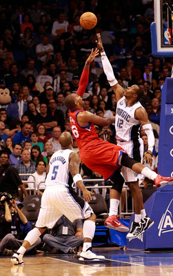 ORLANDO, FL - DECEMBER 18:  Dwight Howard #12 of the Orlando Magic attempts to block the shot of Marreese Speights #16 of the Philadelphia 76ers during the game at Amway Arena on December 18, 2010 in Orlando, Florida.  NOTE TO USER: User expressly acknowl