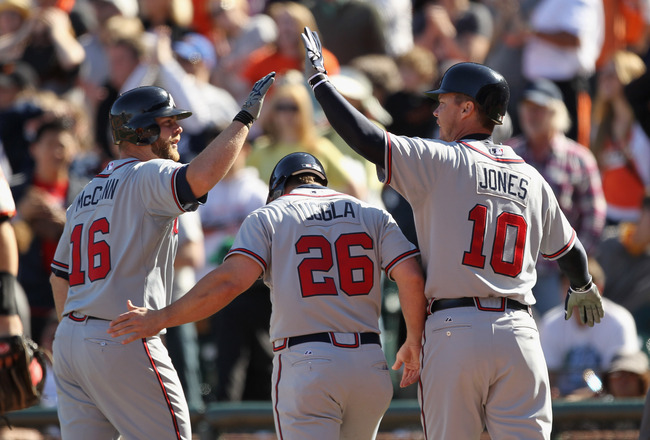 SAN FRANCISCO, CA - APRIL 24:  Brian McCann #16, Dan Uggla #26 and Chipper Jones #10 of the Atlanta Braves celebrate after Uggla and Jones scored in the 10th inning against the San Francisco Giants at AT&T Park on April 24, 2011 in San Francisco, Californ