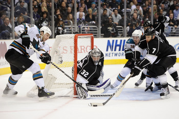 LOS ANGELES, CA - APRIL 25:  Rob Scuderi #7 of the Los Angeles Kings clears the puck from in front of the net in game six of the Western Conference Quarterfinals against the San Jose Sharks during the 2011 NHL Stanley Cup Playoffs at Staples Center on Apr