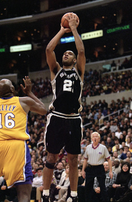 LOS ANGELES - DECEMBER 25:  Tim Duncan #21 of the San Antonio Spurs takes a jump shot as John Salley #16 of the Los Angeles Lakers looks on during the NBA game at the Staples Center on December 25, 1999 in Los Angeles, California. The Lakers defeated the