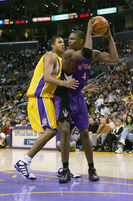 LOS ANGELES - DECEMBER 28:  Chris Bosh #4 of the Toronto Raptors looks to pass around Brian Cook #43 of the Los Angeles Lakers during the game on December 28, 2004 at Staples Center in Los Angeles, California.  The Lakers defeated the Raptors 117-99.  NOT