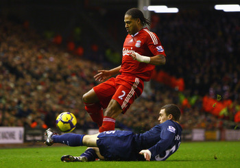 LIVERPOOL, ENGLAND - DECEMBER 13:  Thomas Vermaelen of Arsenal tackles Glen Johnson of Liverpool during the Barclays Premier League match between Liverpool and Arsenal at Anfield on December 13, 2009 in Liverpool, England. (Photo by Clive Brunskill/Getty