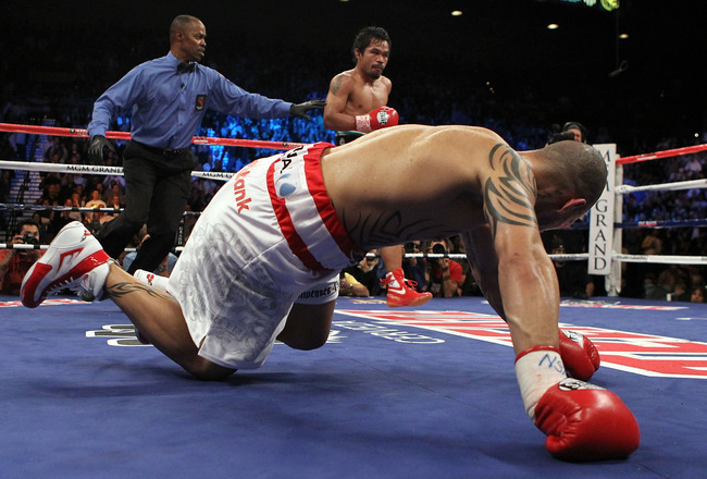 LAS VEGAS - NOVEMBER 14:  (L-R) Manny Pacquiao knocks down Miguel Cotto during their WBO welterweight title fight at the MGM Grand Garden Arena on November 14, 2009 in Las Vegas, Nevada.  (Photo by Al Bello/Getty Images)