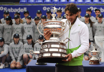 BARCELONA, SPAIN - APRIL 24:  Rafael Nadal of Spain bites the trophy after beating David Ferrer during the final match on day seven of the ATP 500 World Tour Barcelona Open Banco Sabadell 2011 tennis tournament at the Real Club de Tenis on April 24, 2011