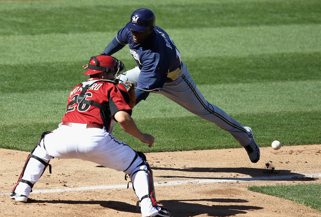 SCOTTSDALE, AZ - MARCH 09:  Brandon Boggs #12 of the Milwaukee Brewers safely scores a run past catcher Miguel Montero #26 of the Arizona Diamondbacks during the fifth inning of the spring training game at Salt River Fields at Talking Stick on March 9, 20