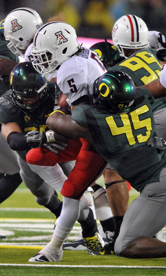 EUGENE, OR - NOVEMBER 26: Running back Nic Grigsby #5 of the Arizona Wildcats is tackled by defensive end Terrell Turner #45 and defensive tackle Zac Clark #99 of the Oregon Ducks in the fourth quarter of the game at Autzen Stadium on November 26, 2010 in