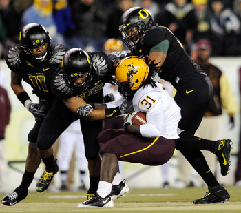 EUGENE,OR - NOVEMBER 14: Linebacker Eddie Pleasant #11, linebacker Spencer Paysinger #35 and linebacker Kenny Rowe #58 of the Oregon Ducks gang up to tackle running back Dimitri Nance #31of the Arizona State Sun Devils in the third quarter of the game at