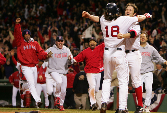 BOSTON - OCTOBER 18:  Johnny Damon #18 of the Boston Red Sox  celebrates with teammate Doug Mientkiewicz #13 and the rest of the Red Sox team after scoring the game winning run on a single hit by David Ortiz #34 in the fourteenth inning to defeat the New