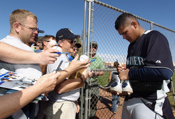 PEORIA, AZ - FEBRUARY 15:  Pitcher Felix Hernandez #34 of the Seattle Mariners signs autographs for fans during a MLB spring training practice at Peoria Stadium on February 15, 2011 in Peoria, Arizona.  (Photo by Christian Petersen/Getty Images)