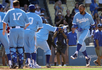 LOS ANGELES, CA - APRIL 21:  Matt Kemp (R) #27 of the Los Angeles Dodgers celebrates with his teammates at home plate after hitting a two-run home run to win the game in the 12th inning against the Atlanta Braves at Dodger Stadium on April 21, 2011 in Los