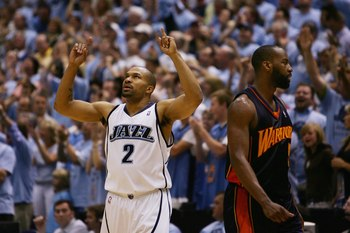 SALT LAKE CITY - MAY 9:  Baron Davis #5 of the Golden State Warriors walks to the sidelines as Derek Fisher #2 of the Utah Jazz celebrates in the closing minutes of overtime in Game Two of the Western Conference Semifinals during the 2007 NBA Playoffs at