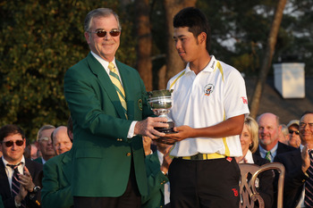 AUGUSTA, GA - APRIL 10:  William Porter Payne (L) presents a trophy to the leading amateur Hideki Matsuyama of Japan during the final round of the 2011 Masters Tournament on April 10, 2011 in Augusta, Georgia.  (Photo by David Cannon/Getty Images)