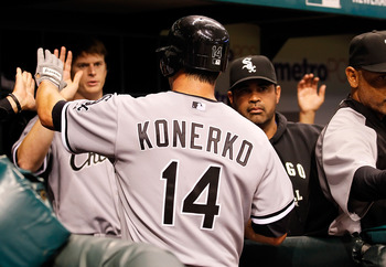 ST. PETERSBURG, FL - APRIL 21:  Infielder Paul Konerko #14 of the Chicago White Sox is congratulated by his teammates after scoring a run against the Tampa Bay Rays during the game at Tropicana Field on April 21, 2011 in St. Petersburg, Florida.  (Photo b