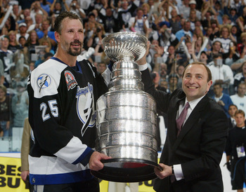 TAMPA, FL - JUNE 7:  Dave Andreychuk #25 of the Tampa Bay Lightning receives the Stanley Cup from NHL commissioner Gary Bettman after defeating the Calgary Flames 2-1 in game seven of the NHL Stanley Cup Finals on June 7, 2004 at the St. Pete Times Forum