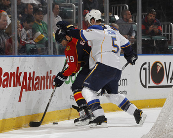 SUNRISE, FL - FEBRUARY 8: Barret Jackman #5 of the St. Louis Blues checks Marty Reasoner #19 of the Florida Panthers on February 8, 2011 at the BankAtlantic Center in Sunrise, Florida. The Blues defeated the Panthers 2-1. (Photo by Joel Auerbach/Getty Ima