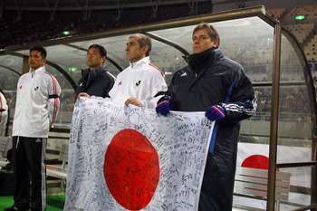 OSAKA, JAPAN - MARCH 29:  J.League XI 'Team As One' team coach, Dragan Stojkjovc holds a signed national flag of Japan  to show support to the earthquake victims prior to a charity match for those affected by the earthquake and tsunami at Nagai Stadium on