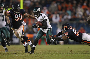 CHICAGO - NOVEMBER 28: Michael Vick #7 of the Philadelphia Eagles breaks a tackle by Lance Briggs #55 of the Chicago Bears as Julius Peppers #90 closes in at Soldier Field on November 28, 2010 in Chicago, Illinois. The Bears defeated the Eagles 31-26. (Ph