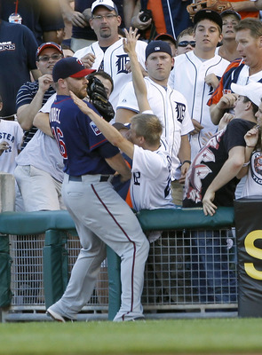 DETROIT - JULY 09:  Jason Kubel #16 of the Minnesota Twins fights with a Tigers fan over a foul ball during the third inning during the game against the Detroit Tigers on July 9, 2010 at Comerica Park in Detroit, Michigan. The Tigers defeated the Twins 7-