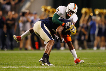 PITTSBURGH - SEPTEMBER 23:  Jon Baldwin #82 of the Pittsburgh Panthers is tackled by Brandon McGee #21 of the Miami Hurricanes on September 23, 2010 at Heinz Field in Pittsburgh, Pennsylvania.  (Photo by Jared Wickerham/Getty Images)