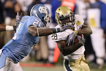 CHARLOTTE, NC - DECEMBER 26:  Dion Lewis #28 of the Pittsburgh Panthers tries to get away from Da'Norris Searcy #21 of the North Carolina Tar Heels during their game on December 26, 2009 in Charlotte, North Carolina.  (Photo by Streeter Lecka/Getty Images