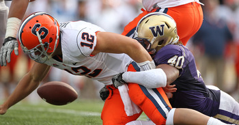 SEATTLE - SEPTEMBER 11:  Quarterback Ryan Nassib #12 of the Syracuse Orange fumbles the ball against Mason Foster #40 of the Washington Huskies on September 11, 2010 at Husky Stadium in Seattle, Washington. The Huskies defeated the Orange 41-20. (Photo by