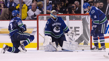 VANCOUVER, CANADA - APRIL 26: Dan Hamhuis #2, goalie Roberto Luongo #1 and Alexandre Burrows #14 of the Vancouver Canucks sit dejectedly on the ice after Jonathan Toews #19 of the Chicago Blackhawks (not pictured) scored the game tieing goal during the th