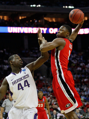 CHARLOTTE, NC - MARCH 18:  Travis Leslie #1 of the Georgia Bulldogs goes up for a dunk and is fouled by Darnell Gant #44 of the Washington Huskies in the first half during the second round of the 2011 NCAA men's basketball tournament at Time Warner Cable