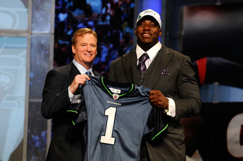 NEW YORK - APRIL 22:  Russell Okung from the Oklahoma State Cowboys poses with NFL Commissioner Roger Goodell (L) as they hold a Seattle Seahawks jersey after he was selected #6 overall by the Seahawks in the first round during the 2010 NFL Draft at Radio
