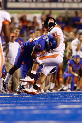 BOISE, ID - SEPTEMBER 25:  Tight end Joe Halahuni #87 of the Oregon State Beavers is tackled by safety Jeron Johnson #23 of the Boise State Broncos at Bronco Stadium on September 25, 2010 in Boise, Idaho.  (Photo by Otto Kitsinger III/Getty Images)