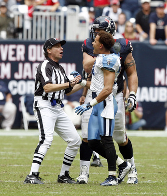 HOUSTON - NOVEMBER 28:  Cornerback Cortland Finnegan #31 of the Tennessee Titans is held back by an official after getting into a fight with Andre Johnson of the Houston Texans at Reliant Stadium on November 28, 2010 in Houston, Texas.  (Photo by Bob Leve