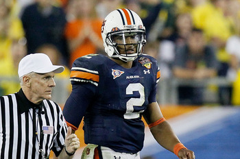 GLENDALE, AZ - JANUARY 10:  Cameron Newton #2 of the Auburn Tigers looks on as an official runs past during their game against the Oregon Ducks during the Tostitos BCS National Championship Game at University of Phoenix Stadium on January 10, 2011 in Glen