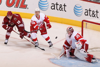 GLENDALE, AZ - APRIL 20:  Brian Rafalski #28 of the Detroit Red Wings clears the puck past goaltender Jimmy Howard #35 while pressed from Lauri Korpikoski #28 of the Phoenix Coyotes in Game Four of the Western Conference Quarterfinals during the 2011 NHL
