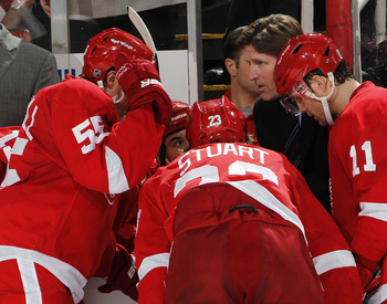 DETROIT, MI - APRIL 16:  Head coach Mike Babcock of the Detroit Red Wings talks with Niklas Kronwall #55, Brad Stuart #23 and Danny Cleary #11 of the Red Wings while playing the Phoenix Coyotes in Game Two of the Western Conference Quarterfinals during th