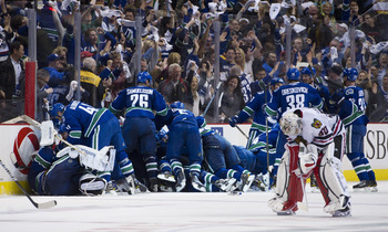 VANCOUVER, CANADA - APRIL 26: The Vancouver Canucks celebrate after defeating the Chicago Blackhawks 2-1 in overtime as goalie Corey Crawford #50 Chicago Blackhawks skates back to his after Game Seven of the Western Conference Quarterfinals during the 201