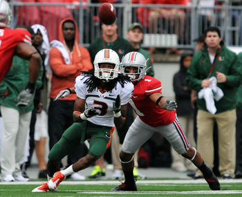 COLUMBUS, OH - SEPTEMBER 11:  Travis Benjamin #3 of the Miami Hurricanes receives a pass as Devon Torrence #1 of the Ohio State Buckeyes defends at Ohio Stadium on September 11, 2010 in Columbus, Ohio.  (Photo by Jamie Sabau/Getty Images)