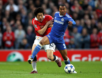 MANCHESTER, ENGLAND - APRIL 12:  Ashley Cole of Chelsea tussles for posession with Ji-Sung Park of Manchester United during the UEFA Champions League Quarter Final second leg match between Manchester United and Chelsea at Old Trafford on April 12, 2011 in