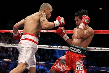 LAS VEGAS - NOVEMBER 14:  (L-R) Miguel Cotto of Puerto Rico throws a right to the head of Manny Pacquiao during their WBO welterweight title fight at the MGM Grand Garden Arena on November 14, 2009 in Las Vegas, Nevada.  (Photo by Al Bello/Getty Images)